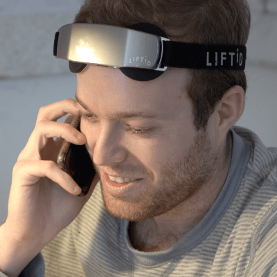 Man Wearing LIFTiD Neurostimulation tDCS device While on Phone